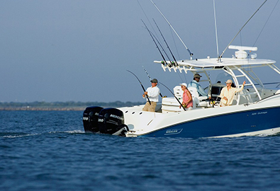 Boston Whaler Outrage in deep blue water with people fishing on it