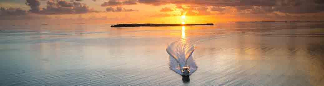 boat running on water with sunset in background