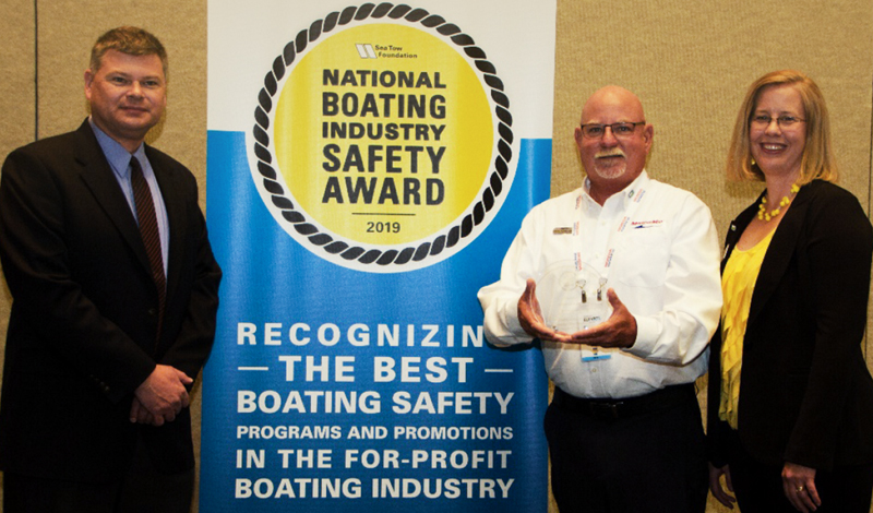 a marinemax team member holding a boating safety trophy