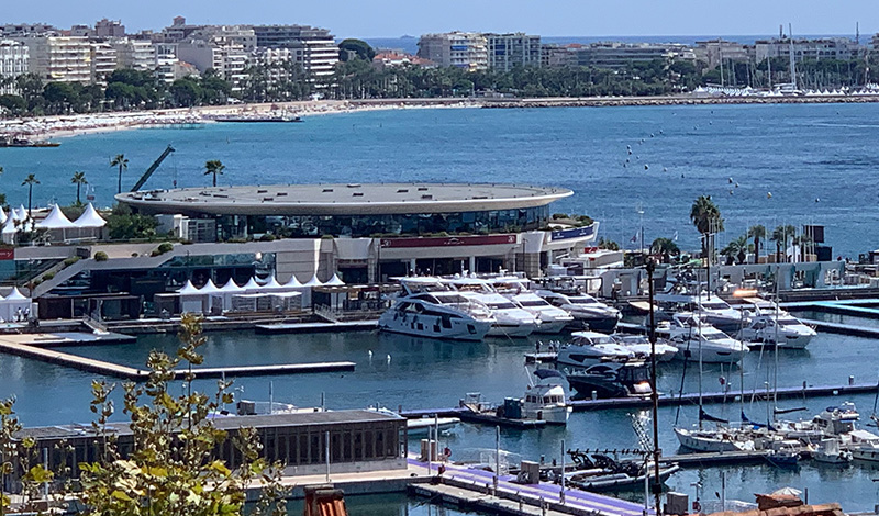 a view of numerous yachts docked at the cannes yachting festival with beaches and buildings along the water in the background