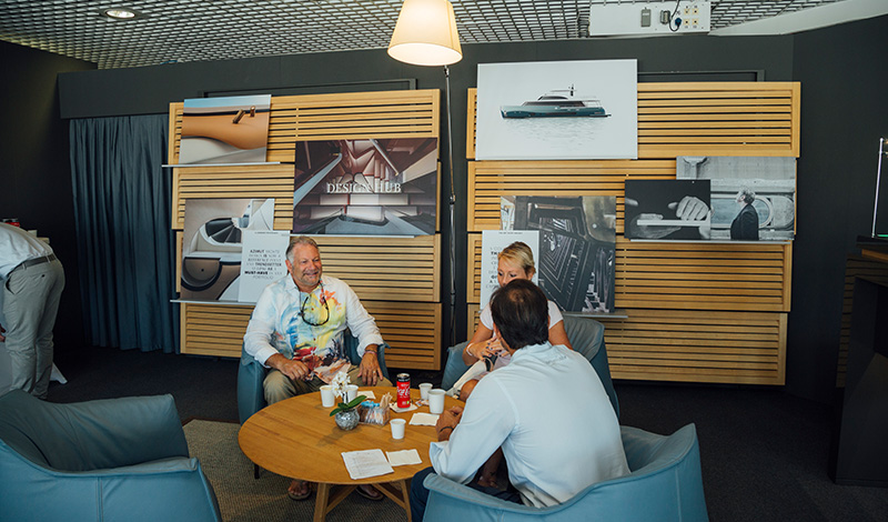 three people seated around a table at a yachting festival with photos of yachts on a wall behind them