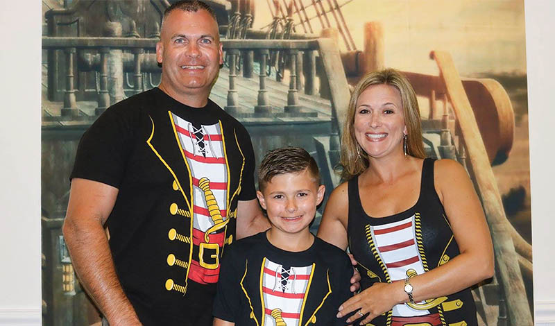 two adults in pirate shirts next to a young boy in a pirate shirt