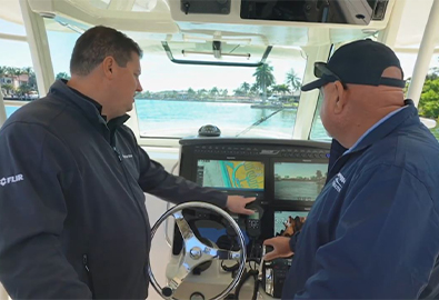 Two men using a Raymarine screen on a boat