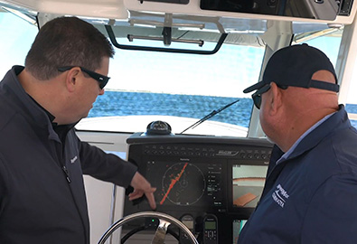 Two men looking at the navigation screen on a boat, as it shows a red diagonal line across the middle.