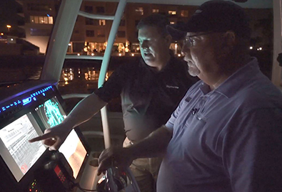 A man in a black polo pointing at a navigation screen on a boat while a man in a blue polo looks ahead and drives