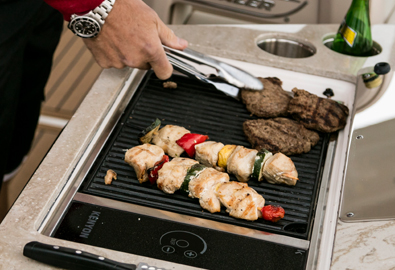 A grill on a boat with meat cooking on it