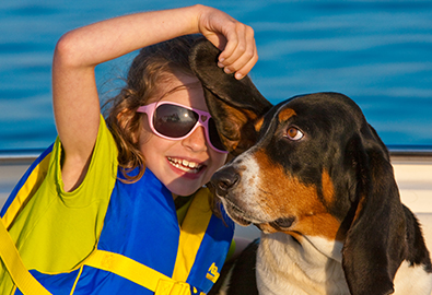 A girl in a blue and yellow life jacket seated next to a black and brown dog on a boat