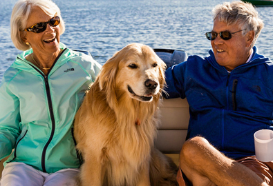 A couple sitting on a boat with a golden retriever sitting between them, with blue water in the background