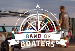"The words ""Band of Boaters"" below a compass logo, with a family on a dock in the background."