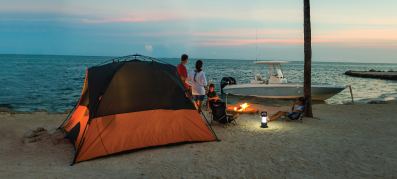 Tent on a beach with a boat in the background at night