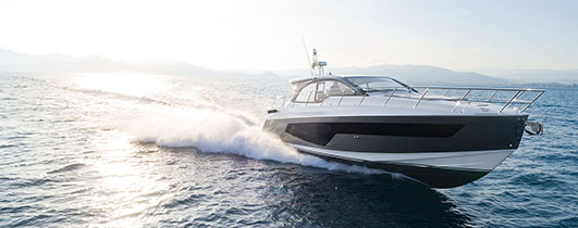 an azimut atlantis 51 cruising through blue water as the sun shines behind it