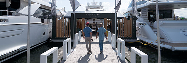two people walking along a dock toward an azimut booth with two azimut yachts on each side at the fort lauderdale international boat show