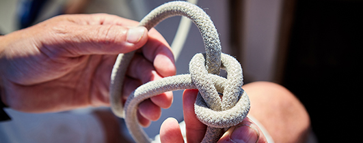 an up close shot of a rope being tied in a knot