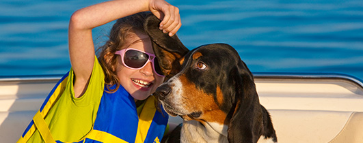 a girl in a blue life jacket seated next to a black and brown dog on a boat