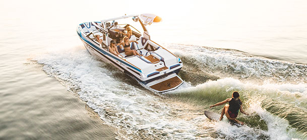 A wakeboarder in the water while being towed by a Tige boat