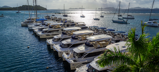 group of boats passing by dock filled with luxurious yachts