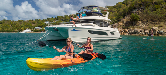 two women kayaking through beautiful aquamarine waters in front of large boat