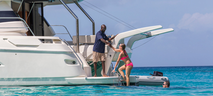 man giving helping hand to woman climbing onto boat from ocean