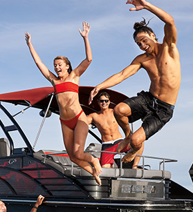 Kids jumping off of a Bennington pontoon boat into the water