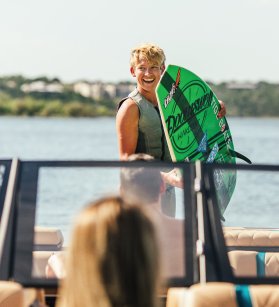 A boy with a wakeboard on a Tige boat