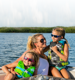 Mom and kids on a boat wearing life jackets for boat safety