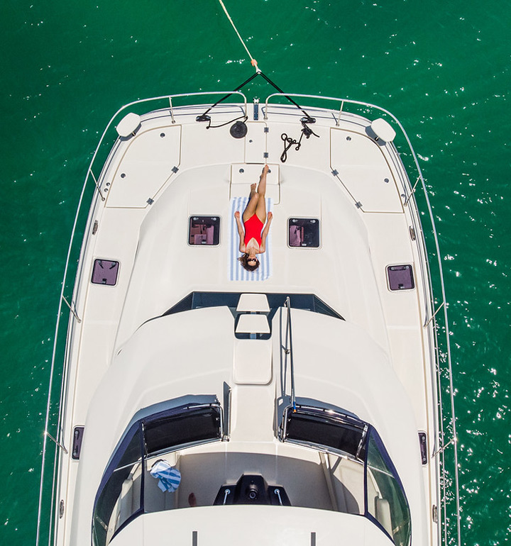 Overhead view of a power catamaran with lady on bow