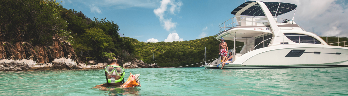 Couple on yacht watches daughter emerge from snorkeling holding a conch shell