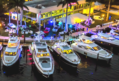 People walking on colorful pier lined with yachts and supercars at marinemax boat show