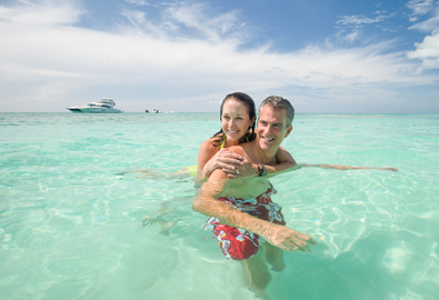 couple in clear water with yacht in background