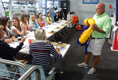 man holding life jacket in front of a group of women sitting at a table