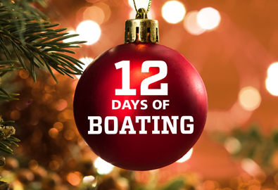 A red Christmas ornament with 12 Days of Boating written on it