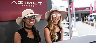 Two ladies sitting at front desk of Azimut boat show booth