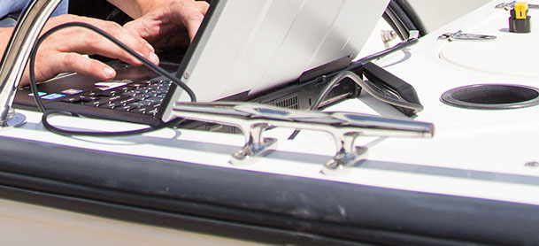 Person typing on a computer on board of a boat