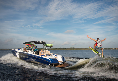 Family watches as man wakeboards behind super air nautique boat