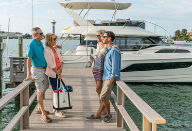 Two couples discussing yacht charters in front of an Aquila yacht