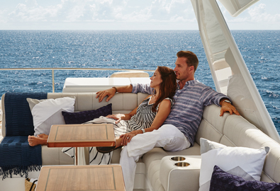 couple lying on luxurious sofa enjoying ocean scenary from deck of their yacht