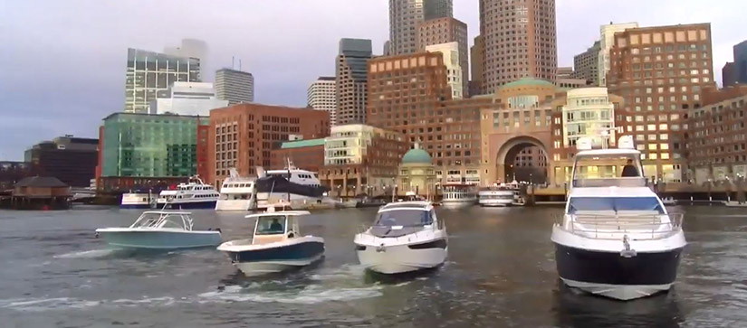 A line of four boats cruising with the Boston skyline behind them
