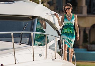 woman in green dress walking along the side edge of a boat