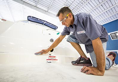 man kneeling on a boat scrubbing the surface