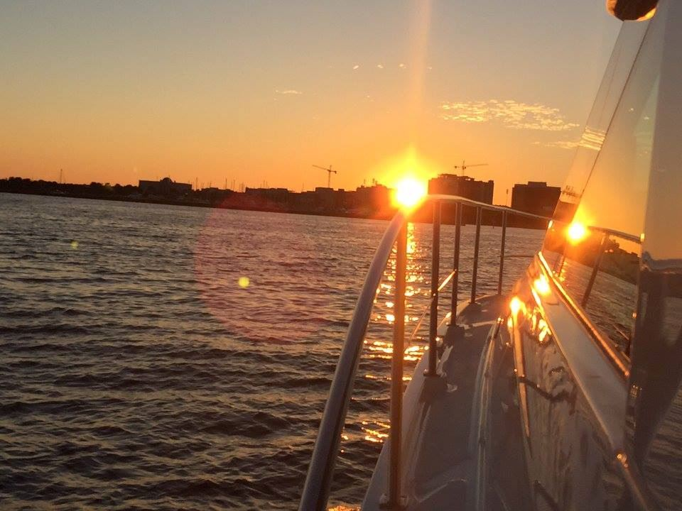 sunset view from side of boat in calm ocean waters