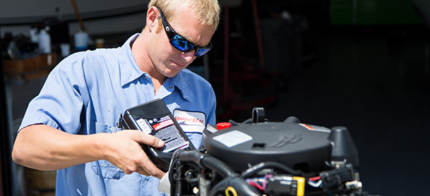 MarineMax Clearwater team member putting oil in engine
