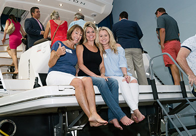 MarineMax Clearwater boat, people boarding it and three ladies sitting on swim platform