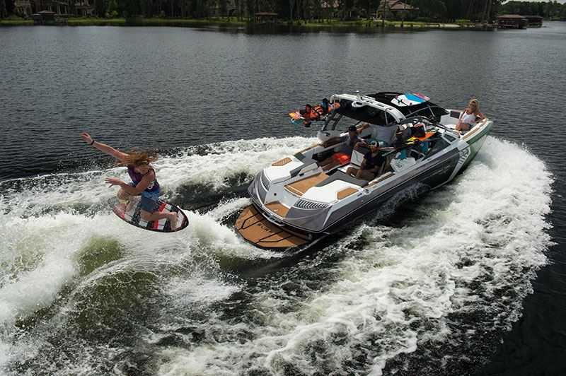 Wake boarding jumping midair while being pulled by a ski boat with friends