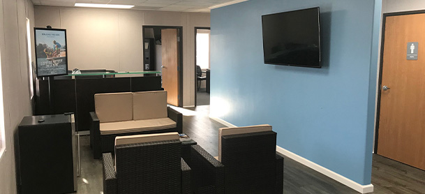 An office with chairs a table and a TV on the wall in the MarineMax Fort Walton Beach office