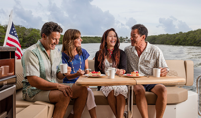 Two couples eating on back of Sea Ray Sundancer 460