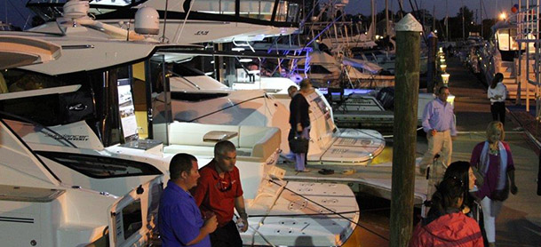 boats tied to dock at night with people walking along the dock