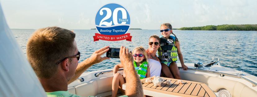 man taking photo of family aboard boat 20 years boating together logo united by water above them