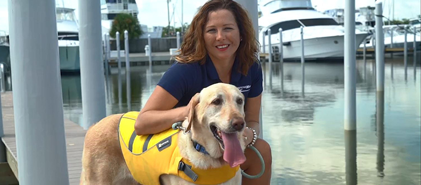 woman squatting next to dog in yellow lifejacket