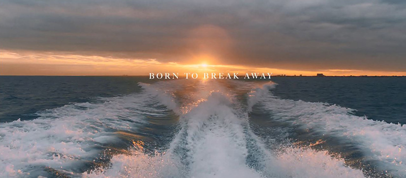 A view off a boat's wake with the sunset behind it, and the words born to break away on the horizon