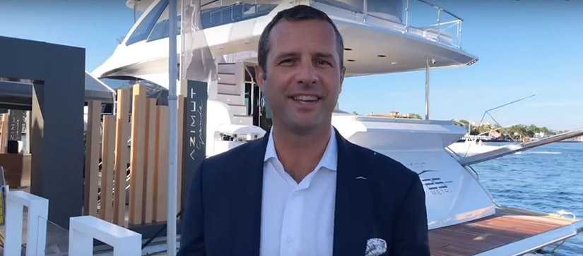 man standing in front of yacht smiling
